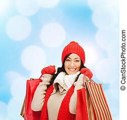 smiling woman in warm clothers with shopping bags - retail...