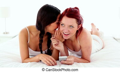 Pretty gleeful women text messaging with smartphone lying on...