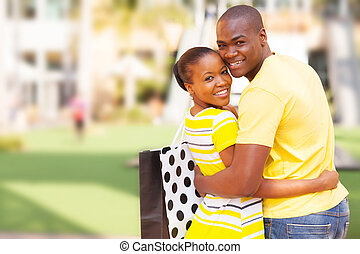 african american couple outside shopping mall - cheerful...