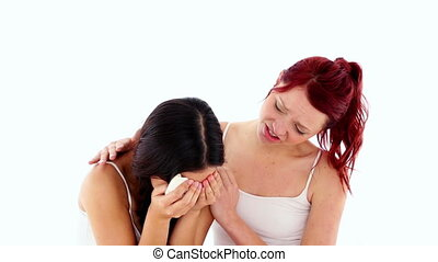Young crying woman being consoled by her friend on white...
