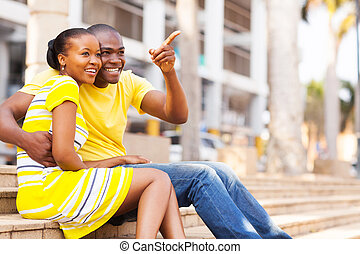 african american couple sitting outdoors in the city - happy...