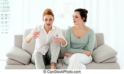 Two attractive women fighting sitting on couch in bright...