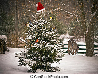 Christmas animals. - A Spruce tree in the snow decorated...