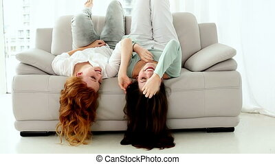 Two lovely women lying head first on couch in bright...