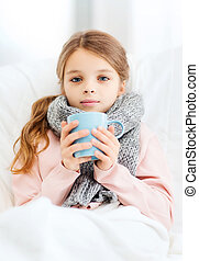 ill girl child with cup of hot tea - healthcare and medicine...