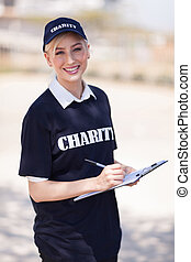 young charity worker writing on clipboard - beautiful young...