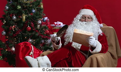 Letter Vs. E-mail - Santa reading a traditional paper letter...