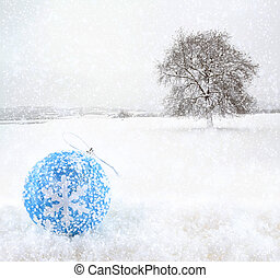 Blue Christmas ball with snowfield as background