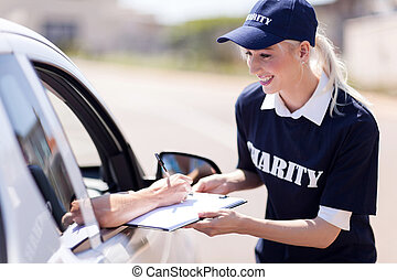 car driver signing a donation papers for charity