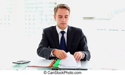 Desperate attractive businessman working sitting at his desk...