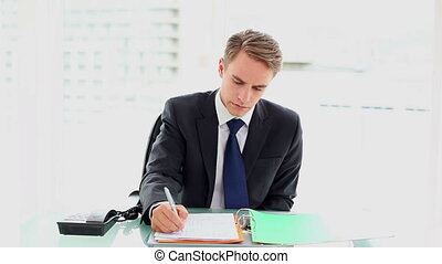 Young annoyed businessman sitting at his desk working in his...