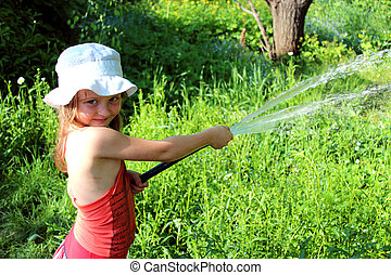 girl watering a kitchen garden in the country