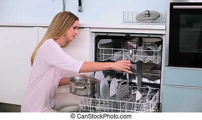 Annoyed woman filling the dish washer in the kitchen