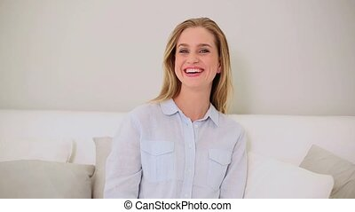 Blonde woman watching television sitting on couch in living...