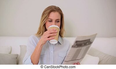 Calm blonde woman reading newspaper