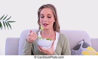 Content blonde woman eating salad s