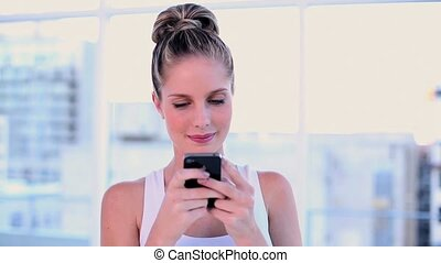 Cute young woman text messaging with her smartphone in...