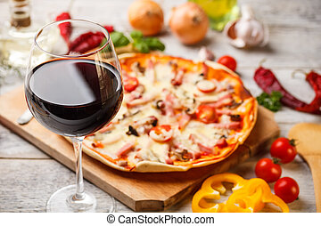 Glass of red wine with pizza on cutting board