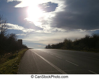Road with dark horizon in evening sun