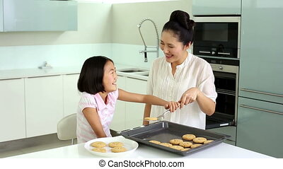 Mother and daughter taking cookies from baking tray in...