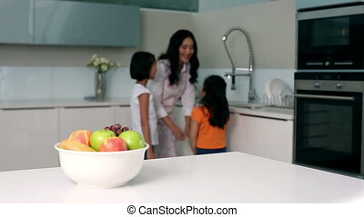 Little girl taking apple out of bowl in bright kitchen
