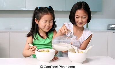 Two girls eating cereal in bright kitchen