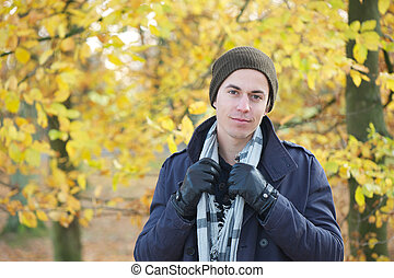 Handsome young man standing outdoors with jacket hat scarf and gloves