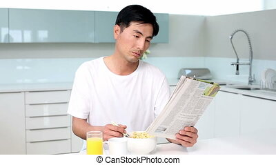 Attractive man eating cereal and reading magazine in bright...