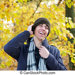 Portrait of a smiling man standing outdoors with hat