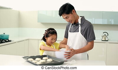 Father and daughter making cookies together at home in the...