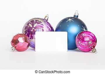 Arrangement of Christmas tree decorations and white card...
