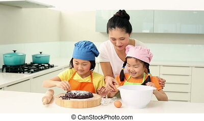 Mother and daughters baking together at home in the kitchen
