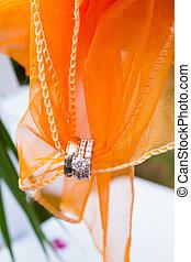 Wedding Rings and Fabric - Orange fabric holds these wedding...