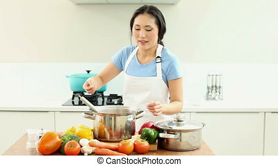 Happy woman seasoning pot and smiling at camera at home in...
