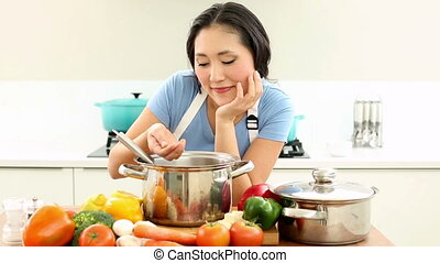 Happy woman stirring pot and smiling at camera at home in...