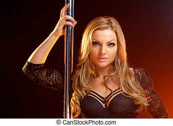 Portrait of a beautiful blond woman with dance pole - Close...