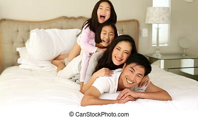 Silly family playing on the bed at home in the bedroom