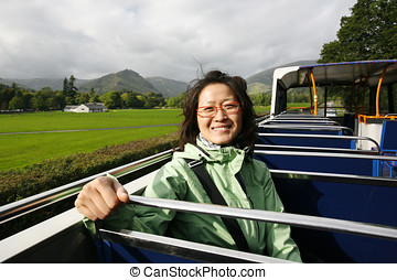 Woman on a tour bus, Lake District - Smiling East Asian...