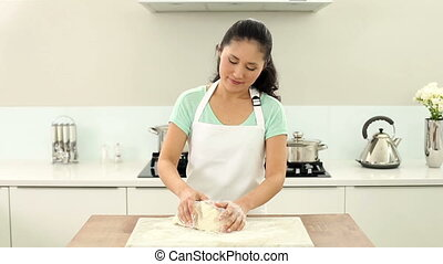 Smiling woman kneading dough at home in the kitchen