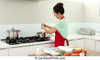 Smiling woman preparing dinner and consulting her recipe...