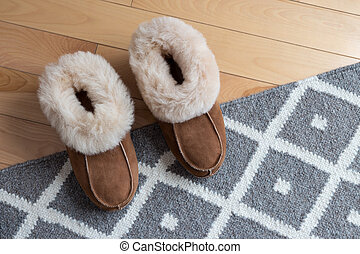 Warm slippers on a rug - Warm comfortable slippers on a gray...