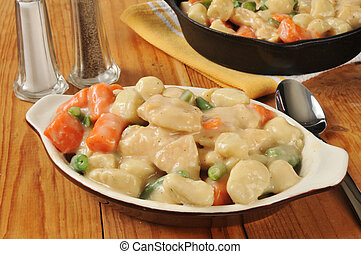 Chicken and dumplings on a rustic wooden table