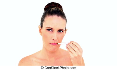 Sick woman using a thermometer on white background