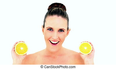 Pretty woman showing two orange halves on white background