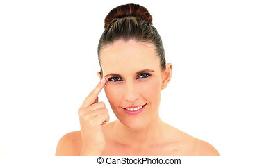 Pretty woman applying face cream on white background