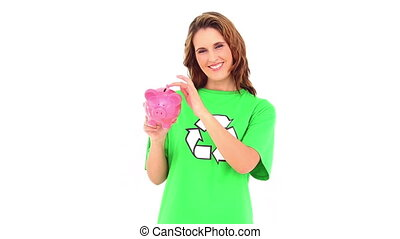 Smiling environmental activist showing piggy bank on white...