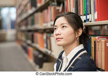 Woman sitting on floor next to bookshelf