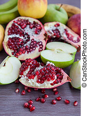 Fresh pomegranate and apples on a wooden table, selective...