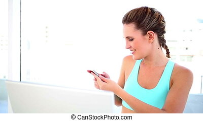 Smiling fit woman sending a text by a bright window