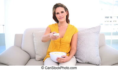 Smiling woman watching tv with popcorn on the couch at home...